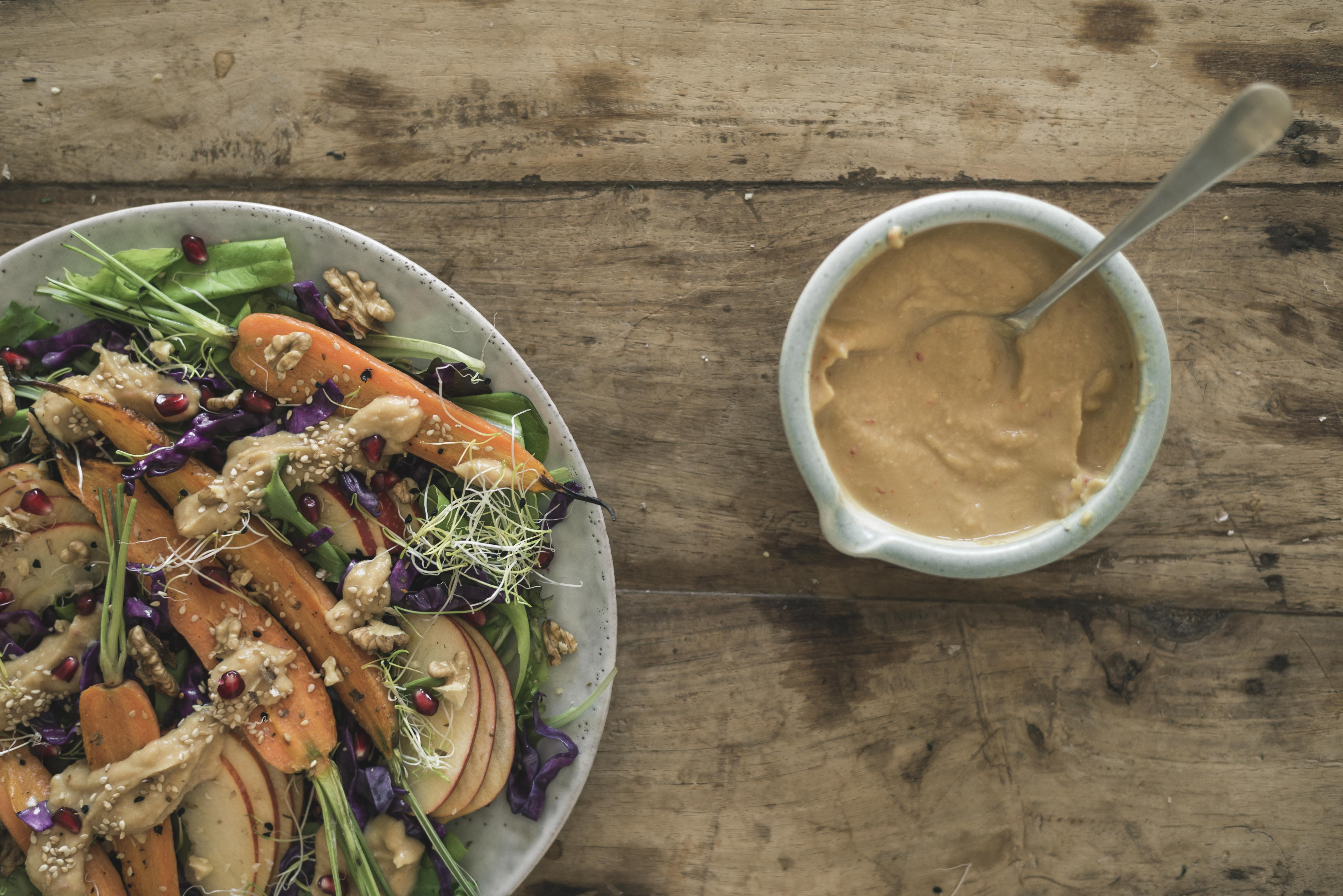 tahini and chickpeas dressing for a fall salad, styled on a wood table